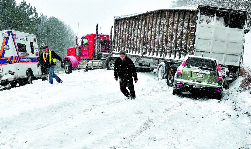 Monday's storm caused this accident on southbound I-95 in Waterville. An occupant of the vehicle, right, trudges up the side of the road as emergency personnel attend to the scene. Three other vehicles slid off the road nearby.