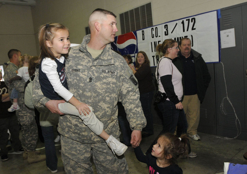 """1st Sgt. John Brooks of Glenburn holds his daughter Elise, 5, and the hand of his daughter Audra, 2, after the return of Bravo Company, 3rd Battalion, 172nd Mountain Infantry in Bangor on Thursday. """"I'm just ready to go home and be called Dad,"""" Brooks said."""