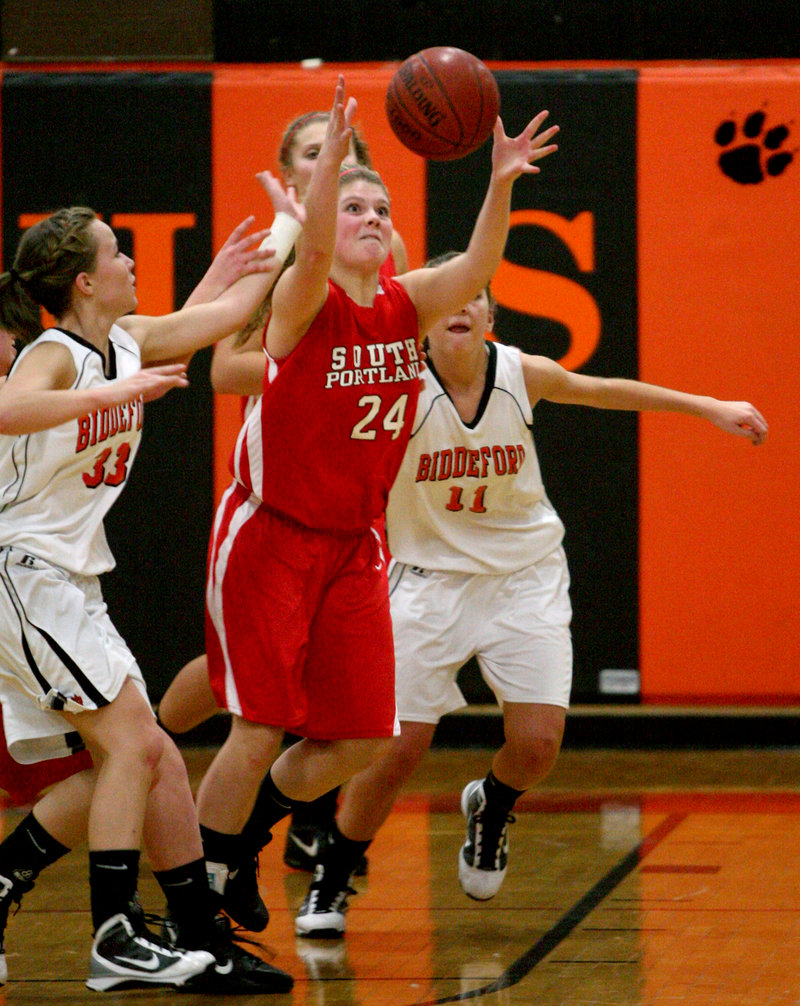 Libby Grant, center, of South Portland outreaches Biddeford's Bryanna Michaud, left, and Alyson Roy for a rebound Friday night in the Red Riots' opening-night win.