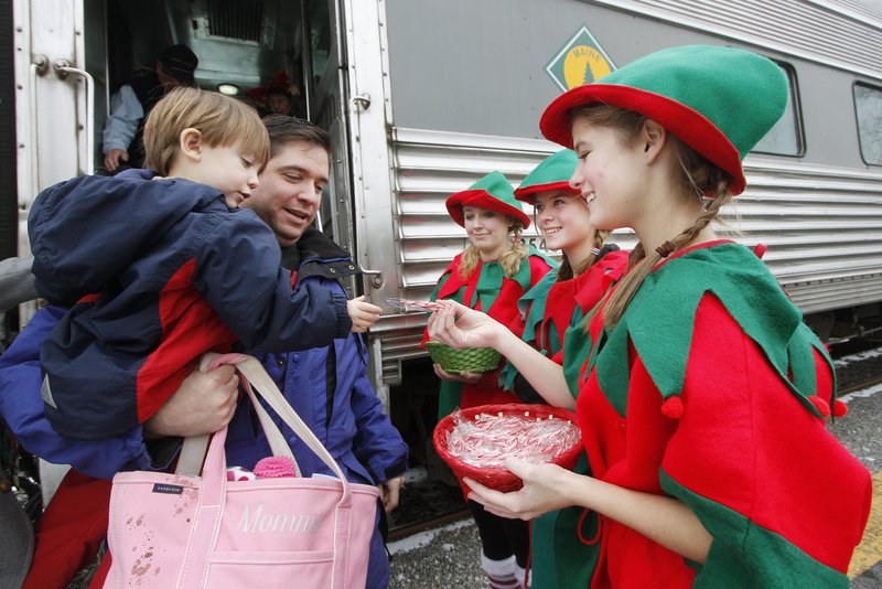Caiden Chase, 2, of Topsham, with his dad Brett, receives a candy cane from Liz Edgerton after the train ride. The other two elves are Nikki Wadlington and Julia Edgerton.