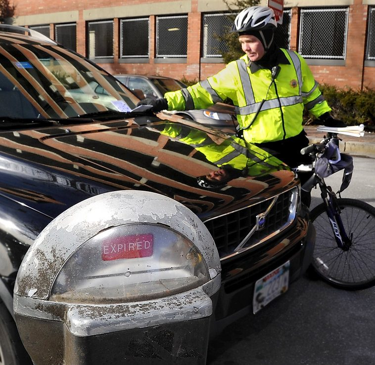 Parking Control Officer Kevin Ready puts a ticket on a car at an expired meter on Free Street in Portland.