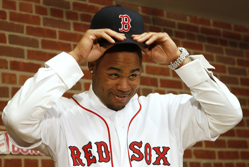 Carl Crawford, trying on his new Boston hat at a press conference Saturday, is a speedy .300 hitter who just might lead the American League in runs scored this year.