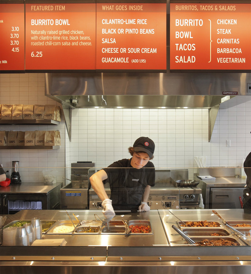 """Kyle Braley stirs a tomatillo green chili salsa at the new Chipotle Mexican Grill in South Portland on Monday, as the franchise restaurant held a """"soft opening"""" for invited customers. The restaurant's grand opening is today."""