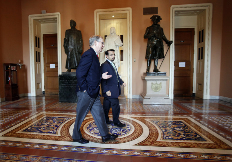 Republican Senate Minority Leader Mitch McConnell, R-Ky., left, walks back to his office with his Deputy Chief of Staff Rohit Kumar following two votes on tax cuts earlier this month.