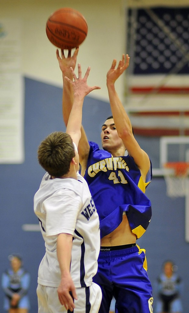 Louie DiStasio of Cheverus releases a 3-point attempt over Ian King of Westbrook. DiStasio had 12 of his 14 points in the first half to help the Stags take control on the way to a 52-35 win.