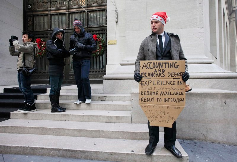 """Jesse Paloger holds up a job-seeking sign Wednesday on Wall Street; the bottom of his sign reads, """"Go-getter from California looking for my shot!"""" Last week, initial claims for unemployment benefits dropped for the third time in four weeks."""