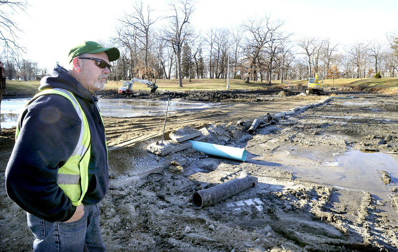 """It is all gross, but this is definitely going to be an improvement,"" says Rick Meserve, supervisor of Portland Public Services, watching as mud is cleared from the Deering Oaks pond on Friday. The removal of the material will expose the pond's original sandy bottom."