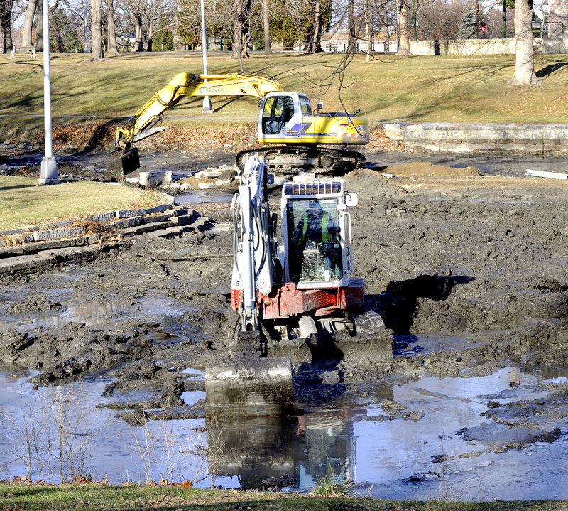 Crews from Portland Public Services use excavators to remove mud Friday from Deering Oaks pond. The project, which will continue next week, was planned to coincide with the annual draining of the water.