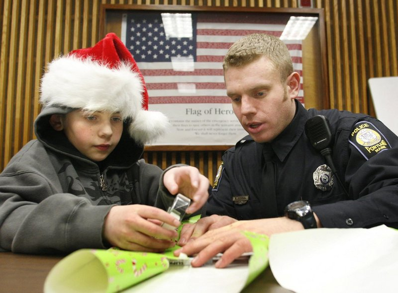 Anthony Troiano wraps a gift with Officer Mathew Dissell at the Portland Police Department. Officers view the program as a fun, stress-free way to spend their day off.