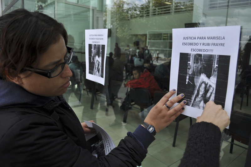 Human rights activists hang a sign on the wall of the state prosecutor's office to protest the killing of Marisela Escobedo in Ciudad Juarez, Mexico, on Friday. Escobedo, was shot in the head Thursday as she protested the unpunished murder of her 16-year-old daughter.