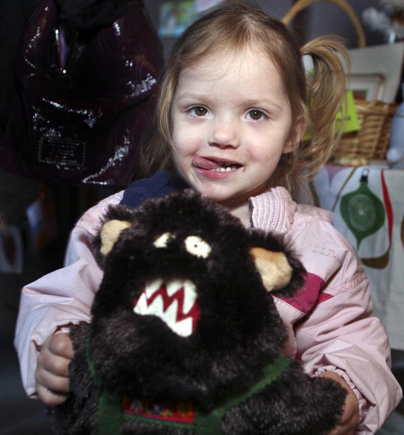 Gabriella Anderson, 2, of Scarborough holds her stuffed Bigfoot at Saturday's Handmade Holiday Craft Fair in Biddeford.