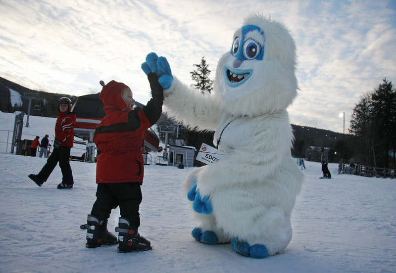 Ian Cushing, 2, of Franklin, Mass., gives Eddy the Yeti a high-five before going skiing for the first time during Winterfest on Saturday.