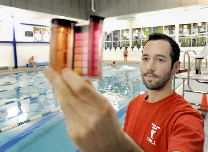 Graham Cavanagh, a lifeguard at the busy YMCA pool on Forest Avenue in Portland, tests the water's pH and chlorine levels. In the past year, the pool reduced the amount of chlorine it uses by 60 percent.