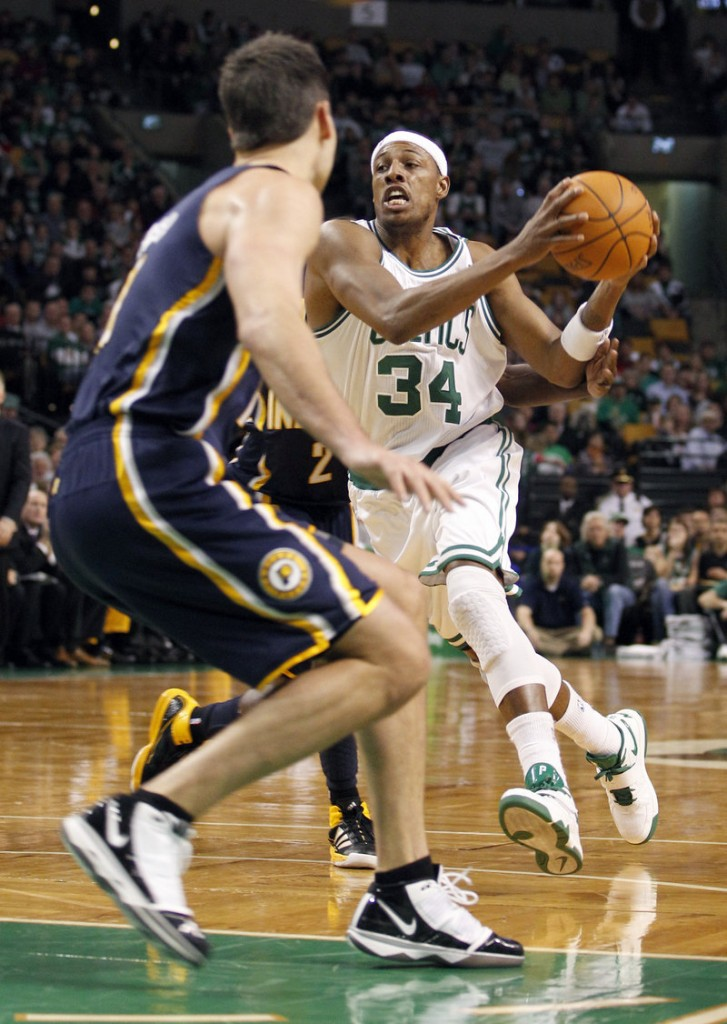 Paul Pierce passes the ball in front of the defense of Indiana's Jeff Foster on Sunday. Pierce had his seventh career triple-double as the Celtics won 99-88.