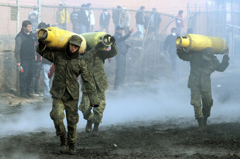 Mexican soldiers remove household gas tanks that survived the fires after a pipeline explosion Sunday in San Martin Texmelucan, Mexico. A pipeline run by the state-owned oil company exploded as thieves were trying to steal either gas or oil, authorities said.