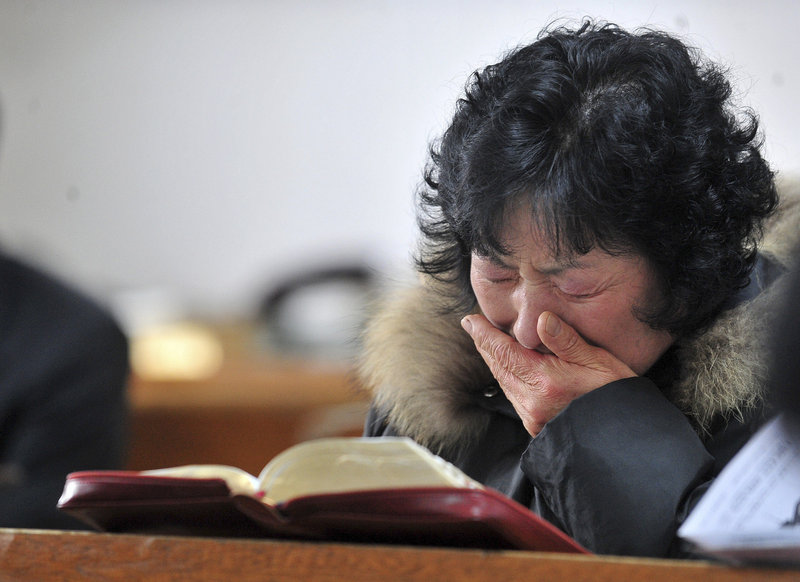 A resident cries during a church service on Yeonpyeong Island, South Korea, on Sunday. Residents were ordered to take shelter underground in advance of military exercises.