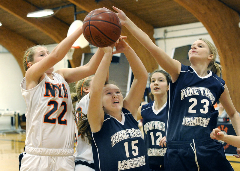 Morgan Scully, left, of North Yarmouth Academy battles for a rebound with Pine Tree Academy s Taylor Johnson, center, and Rebecca Moore-Myshall during NYA's 68-17 victory Monday afternoon.