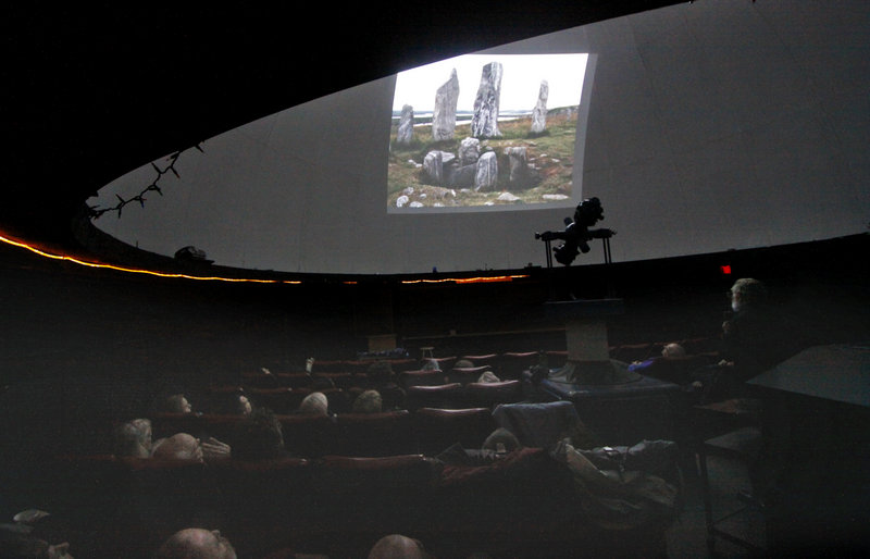 "Patrick Peoples, right, shows a slide of neolithic stones at the University of Maine's Southworth Planetarium on Monday night. Peoples' subject was ""Mid Winter's Eve at Stonehenge,"" but his lecture ranged beyond the famed English monument to include other sites in the British Isles and France."