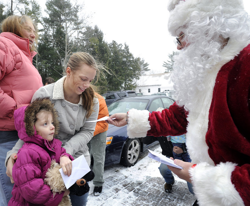 """Secret Santa's helper hands envelopes to Elana Labrecque, 4, and her mother, Erica Labrecque of Sebago. """"This will help us out so much"""" to have a real Christmas, Erica Labrecque said."""