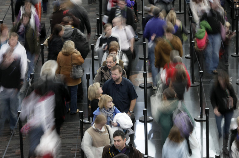 Travelers stand in line Tuesday at a security point at Denver International Airport.