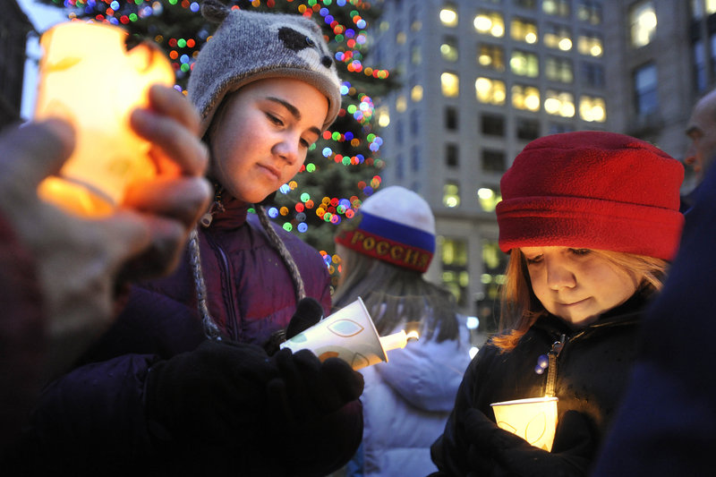 Maeve Porter-Holliday helps light a candle for Sophie Szatkowski, right, during the Homeless Persons Memorial Vigil.