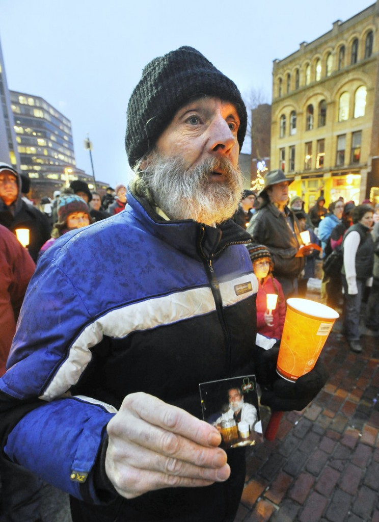 Al Libby, who is homeless, holds a photo of his friend Peter Garland at a vigil in Portland on Tuesday.