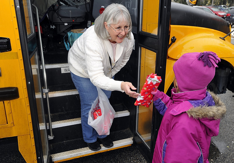 Grace Cole, bus driver for Hall Elementary School in Portland, makes mittens for her passengers every year. Here she gives a pair to Jada Briley, 7, a regular rider who was riding home with her mother on Wednesday.