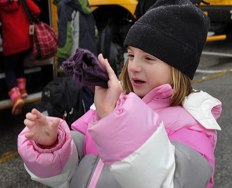 Faith Longval, 8, expresses her joy over the color of the mittens she received from bus driver Grace Cole. Cole says she tries to match the hue of the mittens with the children's coats.