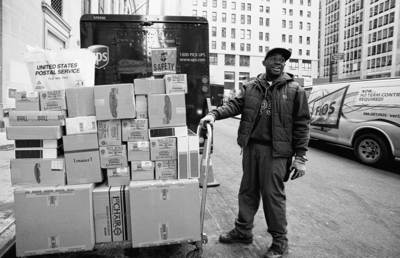 UPS driver Troy Cutkelvin pulls a cart of boxes as he makes his rounds Wednesday in New York. The company expected to deliver a record 24 million shipments worldwide in 24 hours.