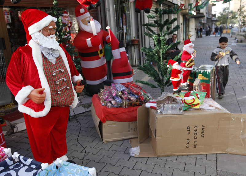 A boy walks past a shop selling Christmas decorations in Baghdad on Wednesday. Church officials in Baghdad, as well as in the northern cities of Kirkuk and Mosul and the southern city of Basra, said they will not put up Christmas decorations or celebrate midnight Mass. An Oct. 31 attack on a Catholic church killed 68 people.