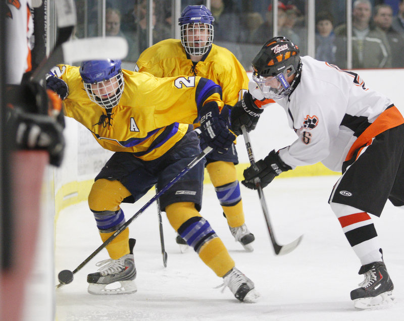 Tim Hanley of Falmouth, left, and Nate Crepeau of Biddeford battle along the boards as William Mullin moves in Wednesday night during their 2-2 tie at the Biddeford Ice Arena.