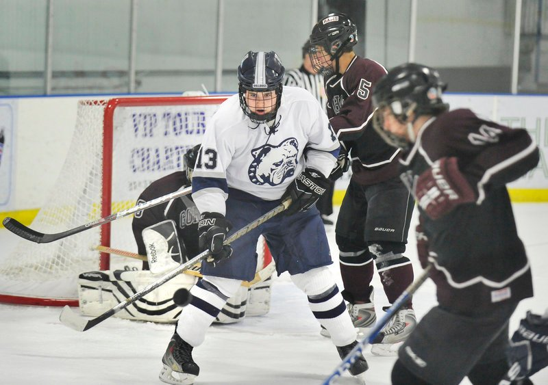 Sam Perdomo of Portland screens Gorham goalie Nate Holloran while a teammate takes a shot Thursday during a Class A hockey game at the Portland Ice Arena. Portland won, 5-2.