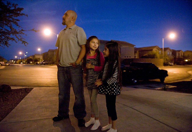 Justin Sanchez, a father of three who used to make $100,000 a year as a carpenter but is now out of work, stands outside his Las Vegas home with daughters Janelle, 8, and Lily, 6, after finding out that his family had three days to vacate their home because of foreclosure. He recently talked to a recruiter about a trucking job in Colorado.