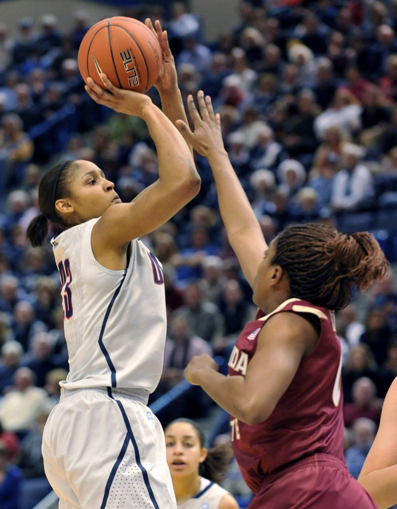 University of Connecticut forward Maya Moore shoots over Florida State forward Chasity Clayton during an NCAA game on Tuesday. Connecticut's win broke a long-held record – a feat barely acknowledged by the media and raising questions about support for women's sports.