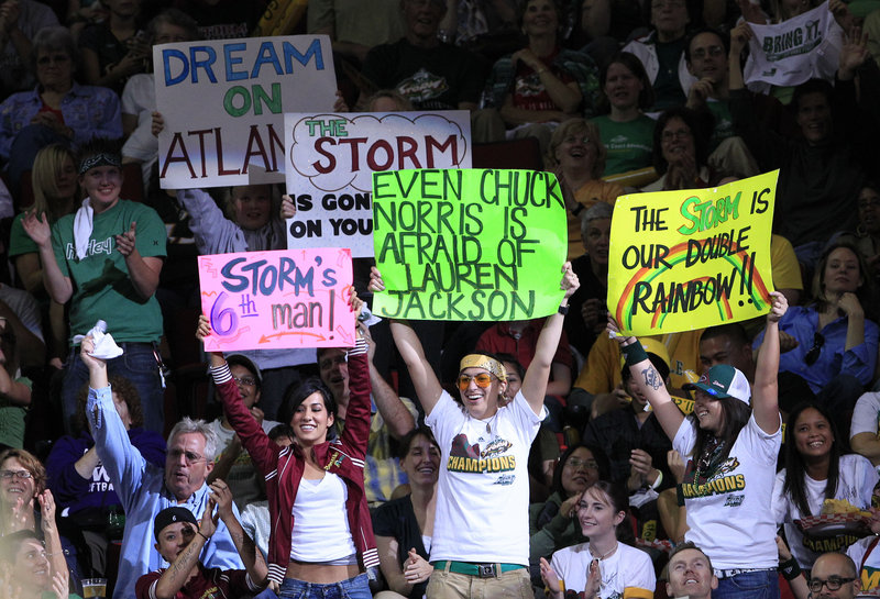Seattle Storm fans cheer on their WNBA team against the Atlanta Dream last fall. Women's sports get much less attention than men's; experts aren't sure why that is.