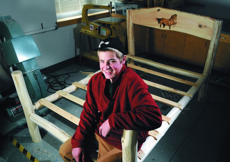 "Gary ""Wes"" Boynton, an eighth-grader at Maranacook Community Middle School, sits on a bed he made from logs. He plans to give the bed to his teacher's daughter for Christmas."
