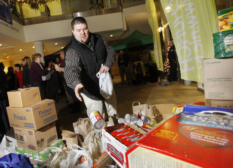 Robert Bisson of Rochester, N.H., drops off canned goods Thursday at a Christmas celebration hosted by the Next Level Church at the University of Southern Maine's Abromson Center. The church, a new Christian congregation in Portland, expected to collect up to 10,000 pounds of nonperishable food items for the Wayside Food Rescue Program.
