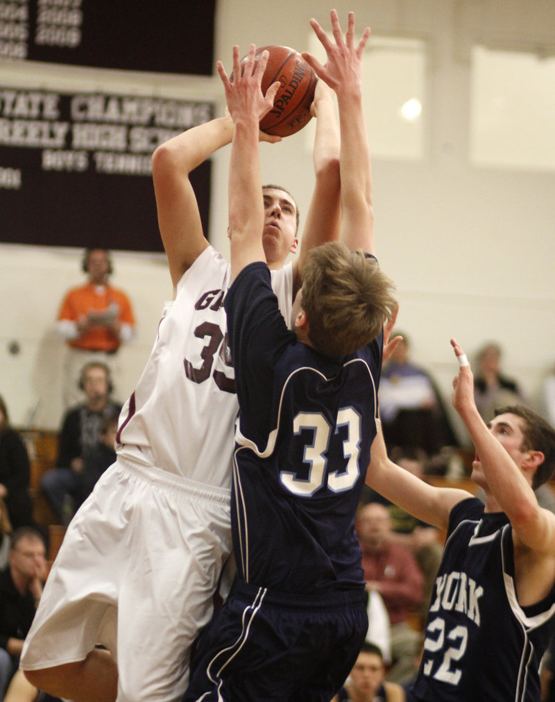 Michael McDevitt of Greely finds just enough room to shoot Thursday night while guarded by Hayden Webster, 33, and Michael King of York during Greely's 67-49 victory at Cumberland.