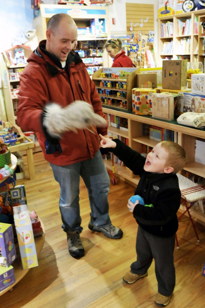 Sean Lyons of Freeport tries out a puppet with his son Nathaniel, 3, at Treehouse Toys. The duo hoped to find the perfect gift for Nathaniel's 9-month-old sister.