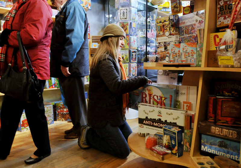 Shanae Carroll of Portland looks through some games Friday at Treehouse Toys in the Old Port, where many stores bustled with shoppers.