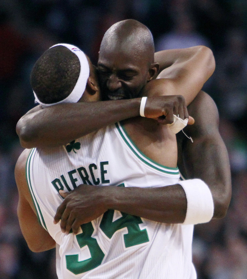 Kevin Garnett hugs Paul Pierce after the Celtics escaped with an 84-80 win over Philadelphia on Wednesday, extending Boston's winning streak to 14 games.