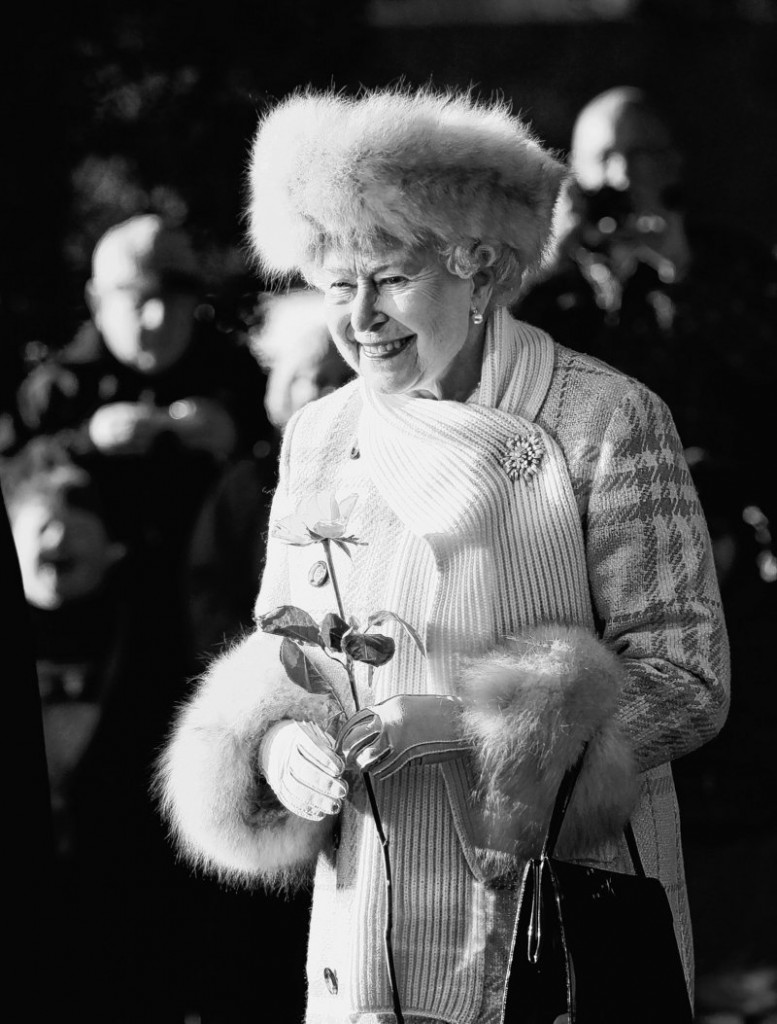 Queen Elizabeth II holds a flower given to her by a young boy as she leaves after attending the British royal family's traditional Christmas Day church service in Sandringham, England.