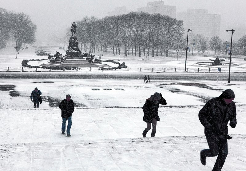Tourists run up the Rocky Steps in front of the Philadelphia Museum of Art after Sunday's snowstorm in Philadelphia postponed the Vikings-Eagles game.