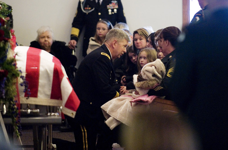 "Brig. Gen. William ""Tim"" Crosby presents the Purple Heart, Bronze Star and the Meritorious Service Medal to the family of Army Sgt. Barry Jarvis, 36, in Tell City, Ind., on Dec. 9. Jarvis, a member of the 101st Airborne Division, was one of six soldiers killed Nov. 29 in Afghanistan when a rogue border police officer turned his gun on his American trainers."