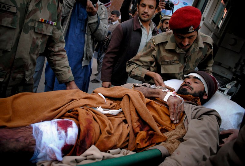 Pakistan army paramedics unload a man injured in a suicide bombing, at a hospital in Peshawar on Saturday. A female bomber killed 45 people outside a World Food Program food distribution center in Khar, triggering a districtwide suspension of the relief project.