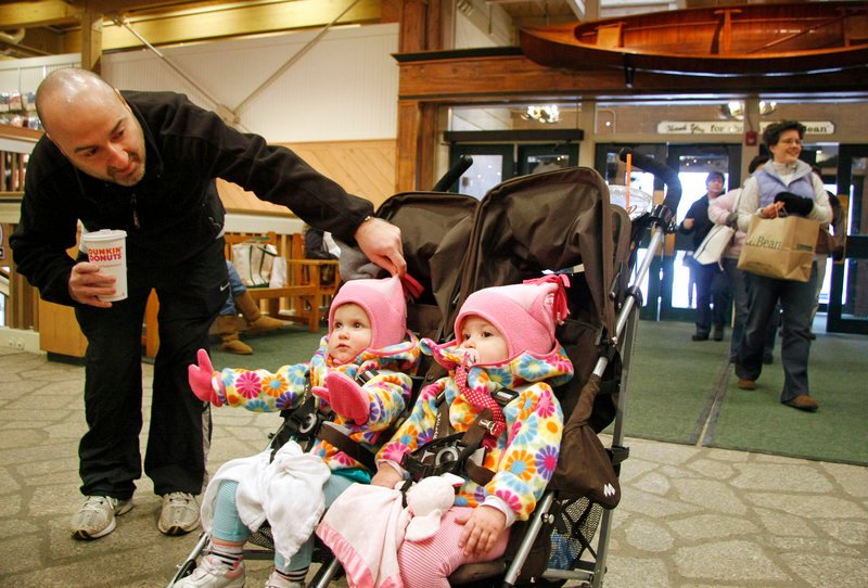 John Scalcione of South Carolina tends to his 18-month-old twins, Anna, left, and Ella, while shopping with his wife, Christina, at L.L. Bean in Freeport on Sunday.