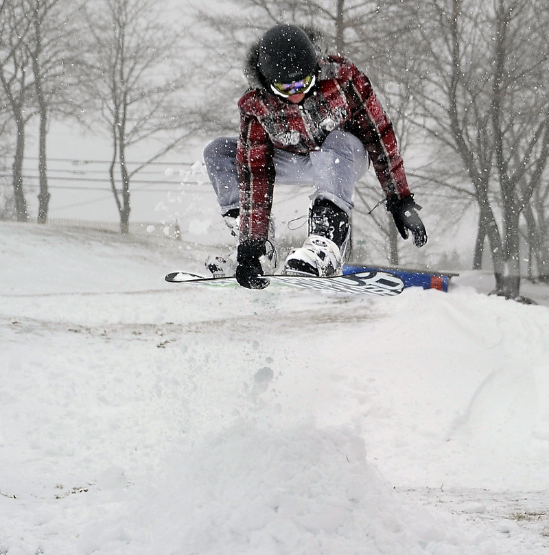Jake Farrell works on an Indy Grab while going off a jump at Payson Park. The foot of snow Portland received recently should fuel the riding.