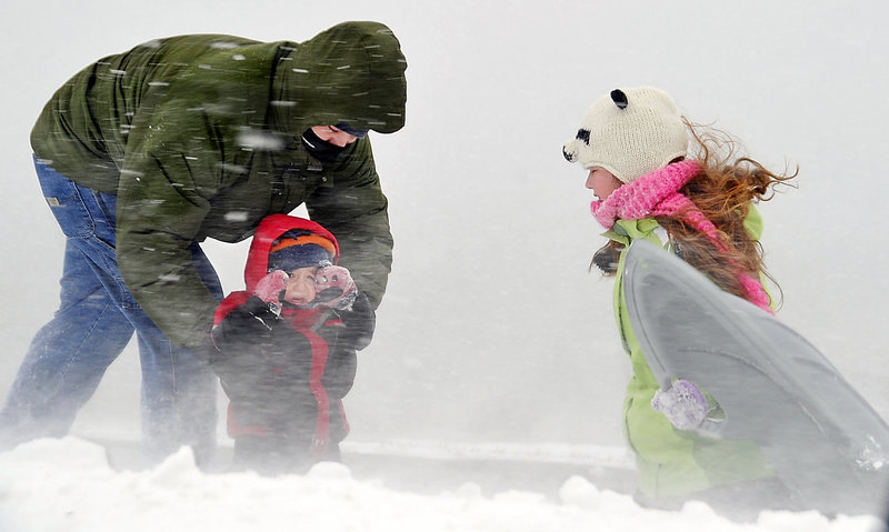 Josh Bankhead of Portland comforts his 3-year-old son, Moses, during a sudden squall of snow and wind on the Eastern Prom as his daughter, Adara, 10, hangs onto her sled blowing in the wind Monday. Cold temperatures and winds are expected to continue today.
