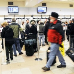 Travelers line up at US Airways at the Portland International Jetport. Under new regulations, flights that might have made an attempt to take off in bad weather in the past are now canceled.