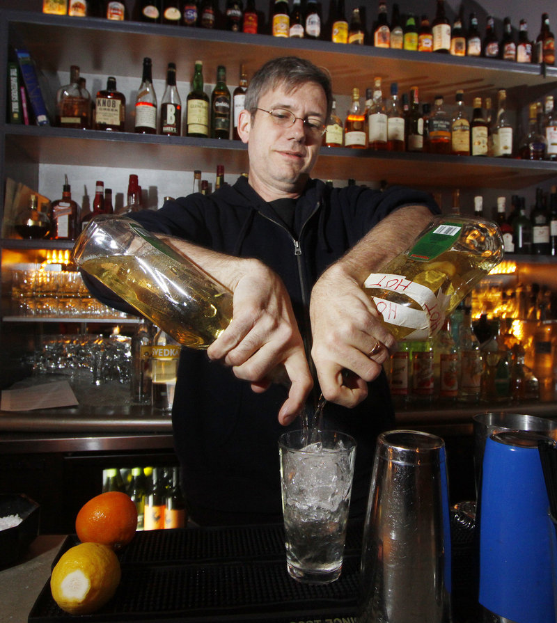 David Allen mixes a mojito at Bandaloop, where the bar area wraps around an exposed kitchen area.
